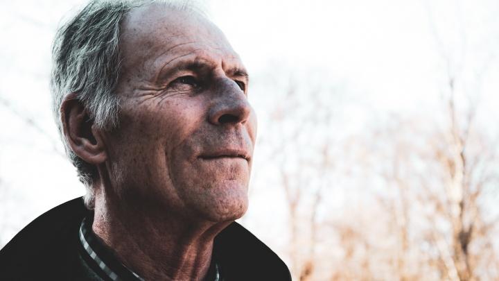 An older man looking ahead.