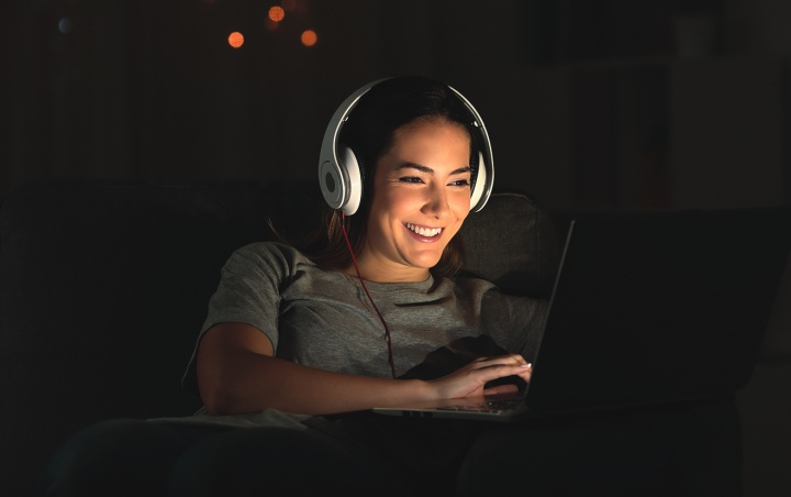 A girl wearing headphones while watching the screen of a laptop.