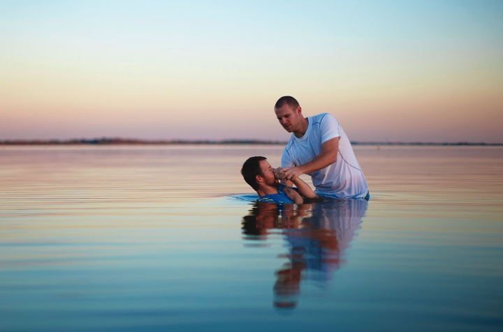 A man putting another man under water.