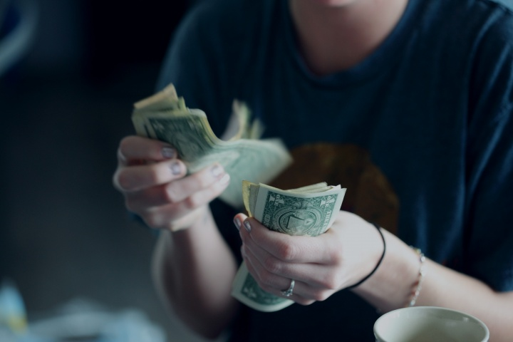 A young woman counting dollar bills.