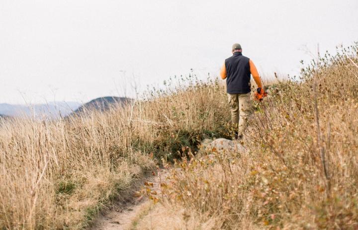 A man walking on a dirt trail.