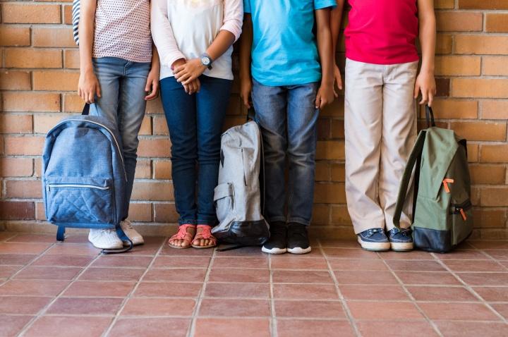 Kids holding backpacks.