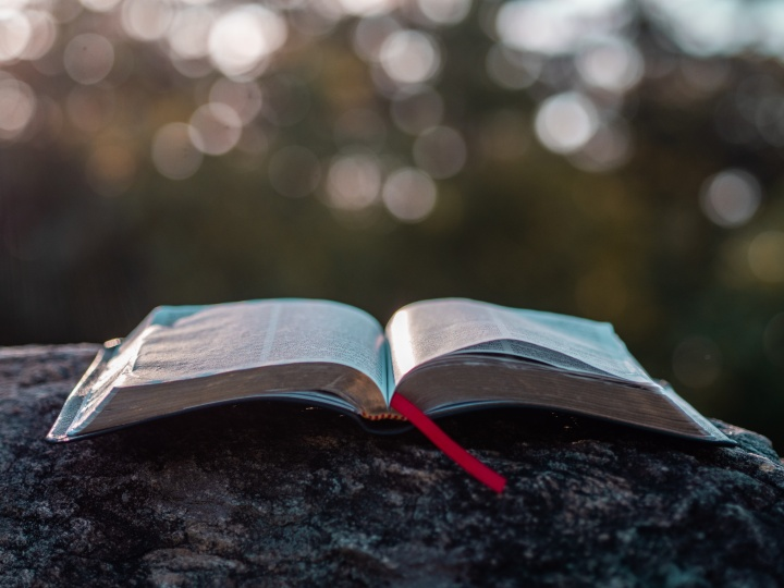 An open Bible laying on a rock.