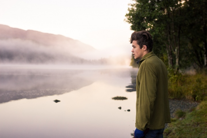 A young man looking out over a lake.