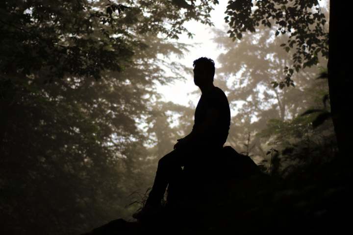 Silhouette of man sitting on a rock.