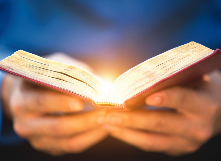 A open Bible emitting rays of light.