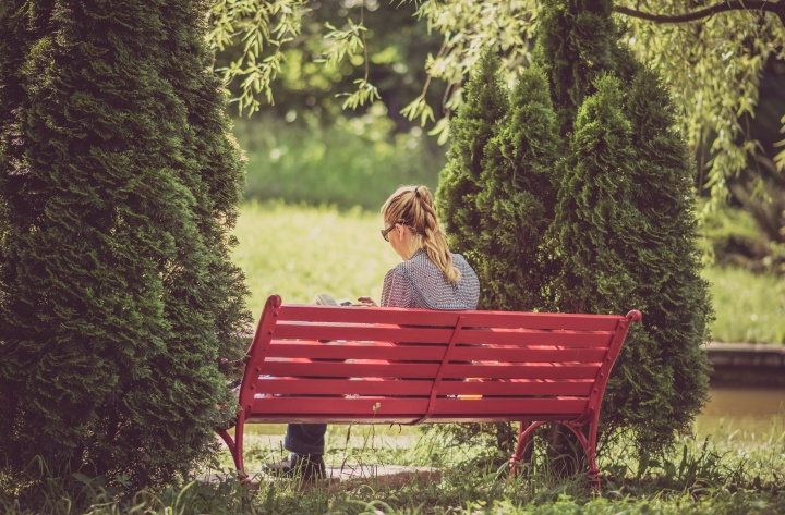 A woman reading while sitting on a red bench.