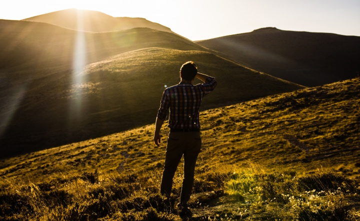 A man looking out over a vista of hills with the sun in his eyes.