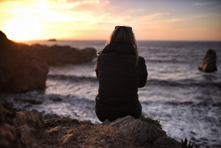 A woman sitting on a rock looking out over water.