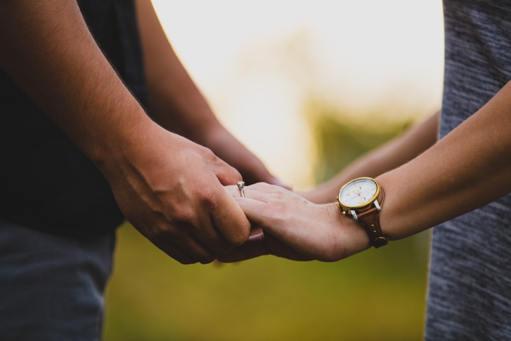Photo of man and woman with wedding rings holding hands.