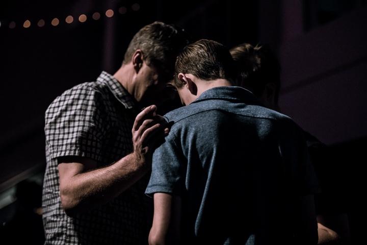 Two men praying together.