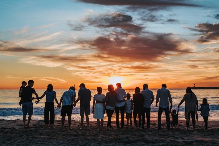 A big family gathering at the beach at sundown.