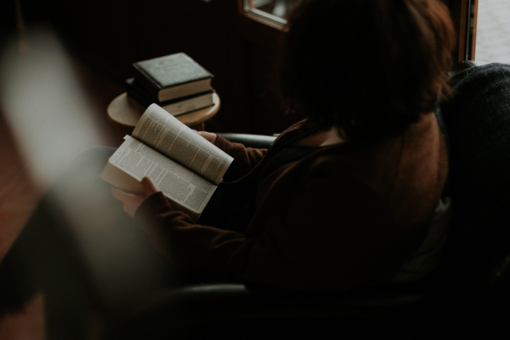 A sitting in a chair reading a Bible.