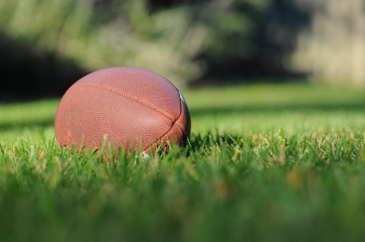An American football on a grass field.