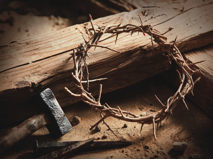 A wooden cross/stake with a crown of thorns, hammer and nails.