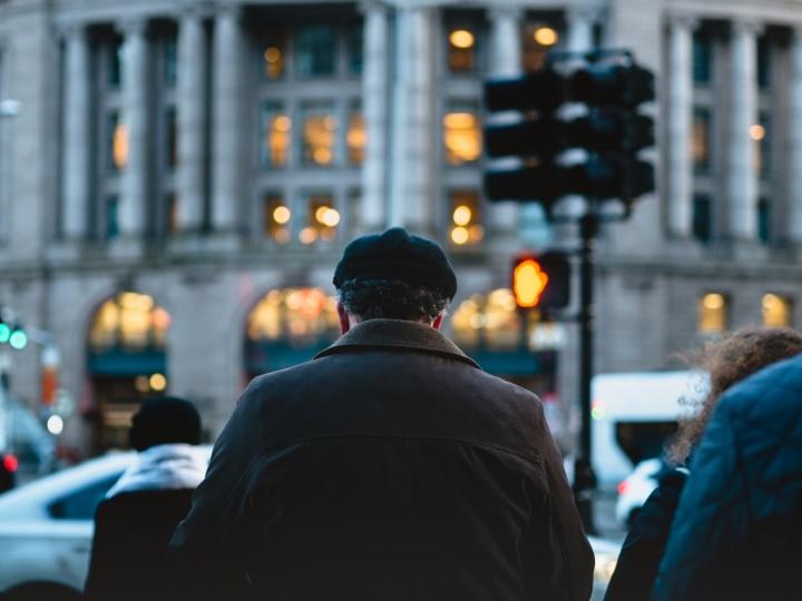 A older man at busy sidewalk.