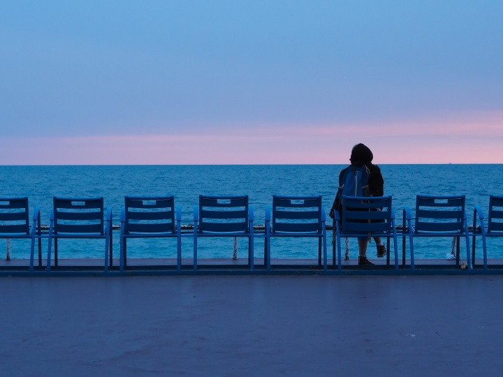 A person sitting watching the water of a sea.