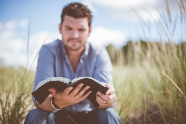 A man reading a Bible outside.