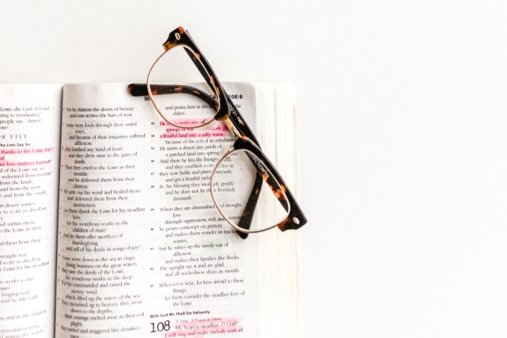 Photo of glasses sitting atop an open Bible.