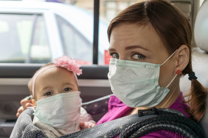 A woman and small child wearing face masks sitting in a car.