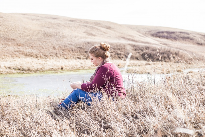 A woman sitting in a field of tall grass.