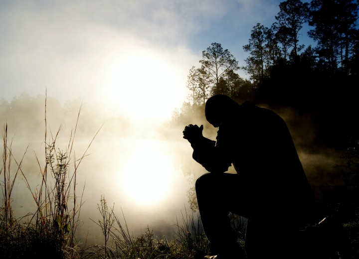 Silhouette of a man praying.
