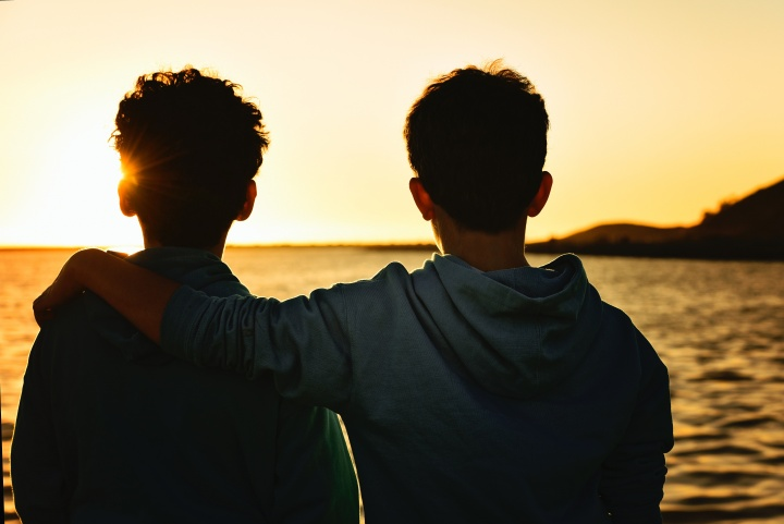 Photo of two boys looking at the sunrise together.