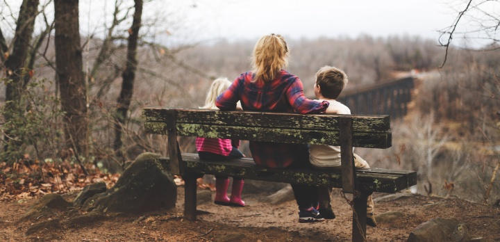 Photo of mother with two children on a bench.