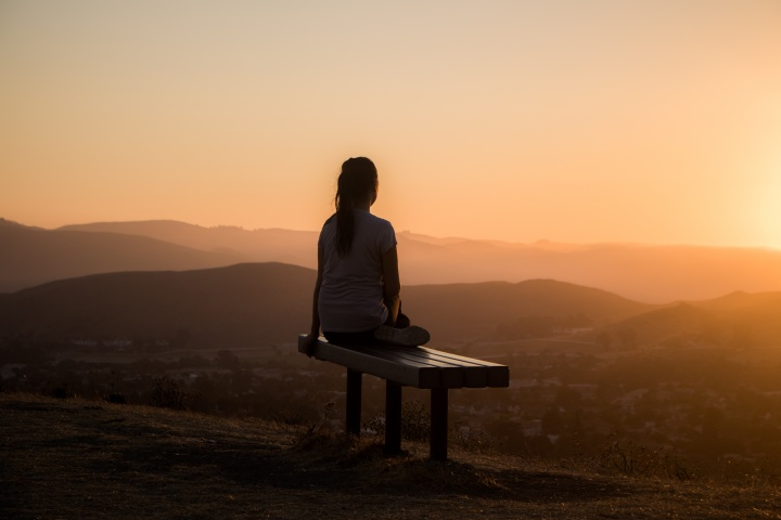 A woman sitting on a bench at sunset.