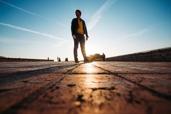 A man walking on a cobblestone sidewalk.