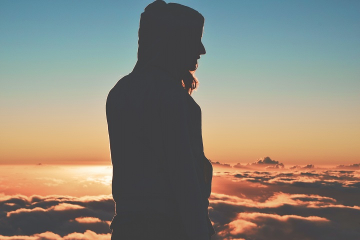A woman on high mountain with clouds behind her.
