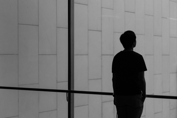 A person looking past a large glass window.