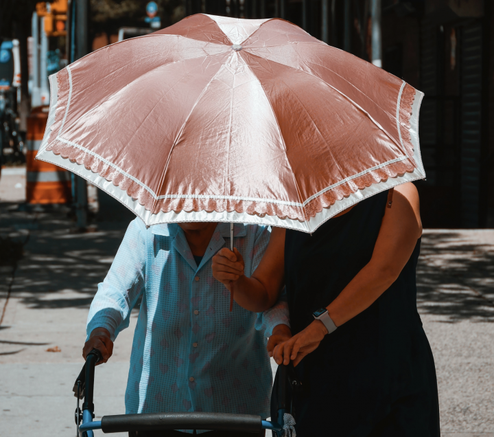 Photo of two women walking under a parasol; an elderly woman with a walker being helped by a middle-aged woman.