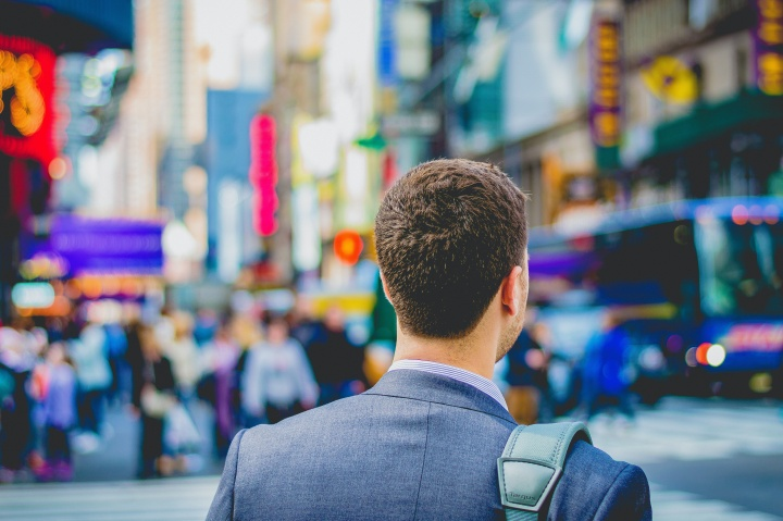 A business man walking in a busy city.