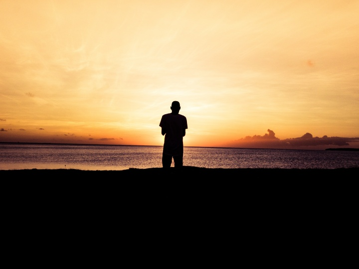 A person standing by a body of water at sunset.