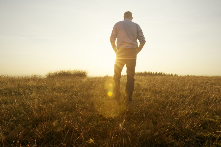 Photo of a man walking in a field toward the sun at golden hour.