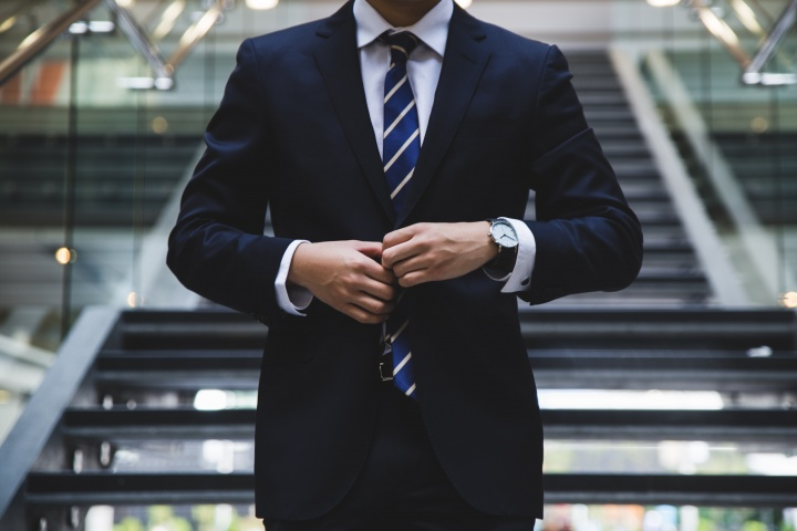 Photo of a man buttoning a tailored suit.