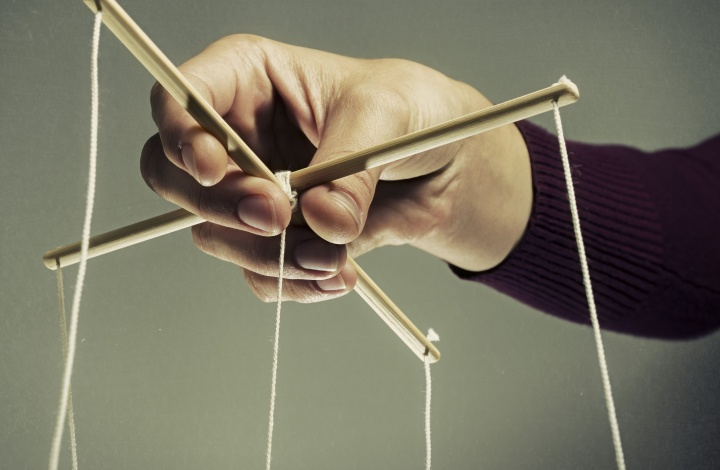 A person holding a puppet strings.