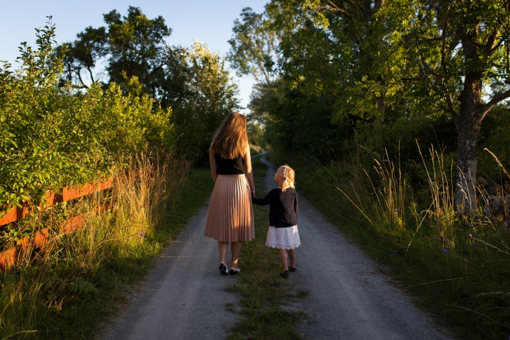 Photo of a mother and young daughter walking down a dirt road in the countryside; the daughter is holding her mother's hand and looking up at her.