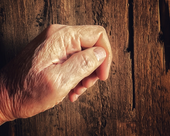 An old hand knocking on a old wooden door.