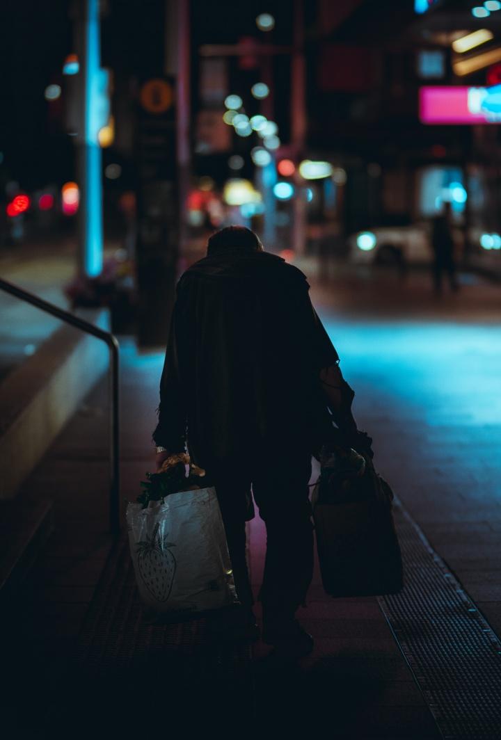 Homeless man walking down street at night under street lights