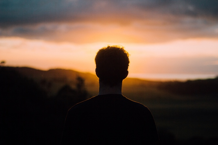 A young man watching the sunset.