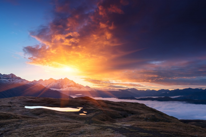Sunrays over a mountain and a lake.