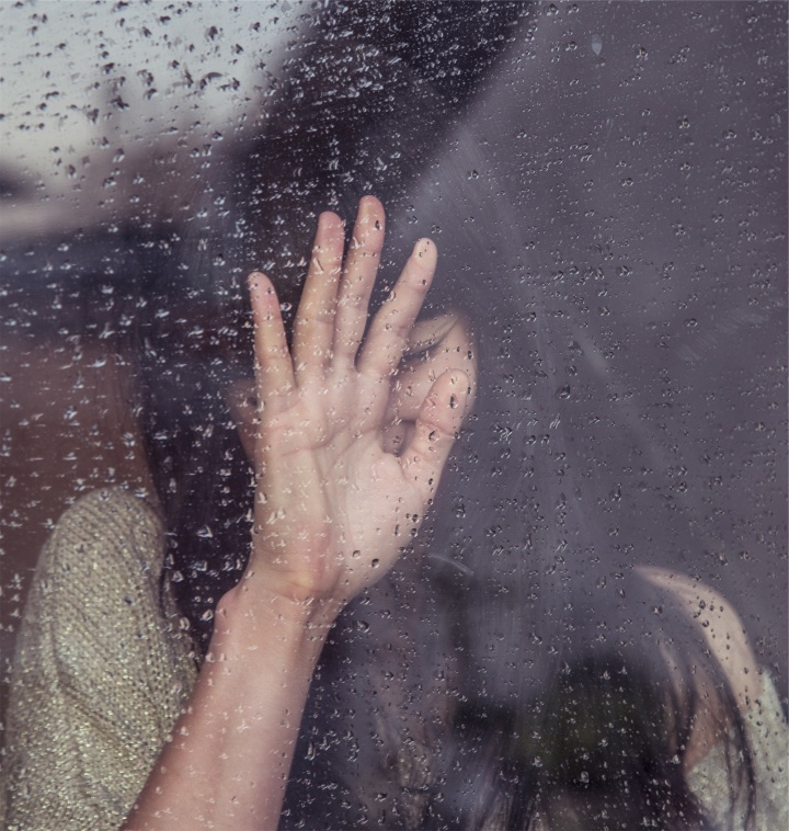 A woman behind a rain covered window.