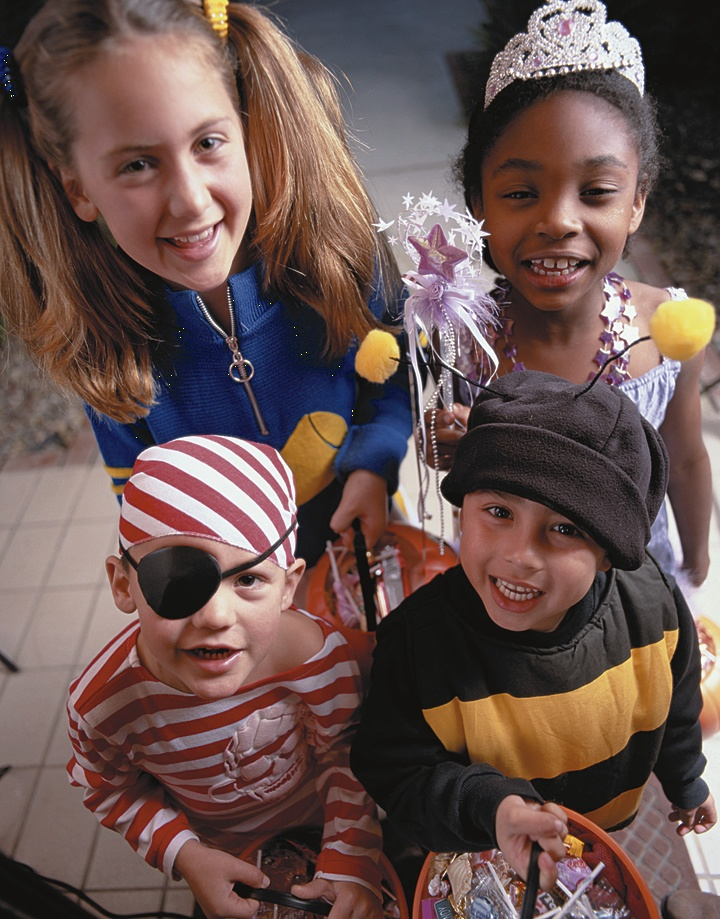 Little kids in costumes trick-or-treating at a house.