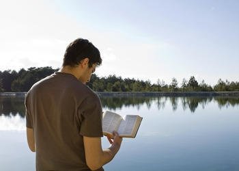 A man reading a Bible outside by a lake.
