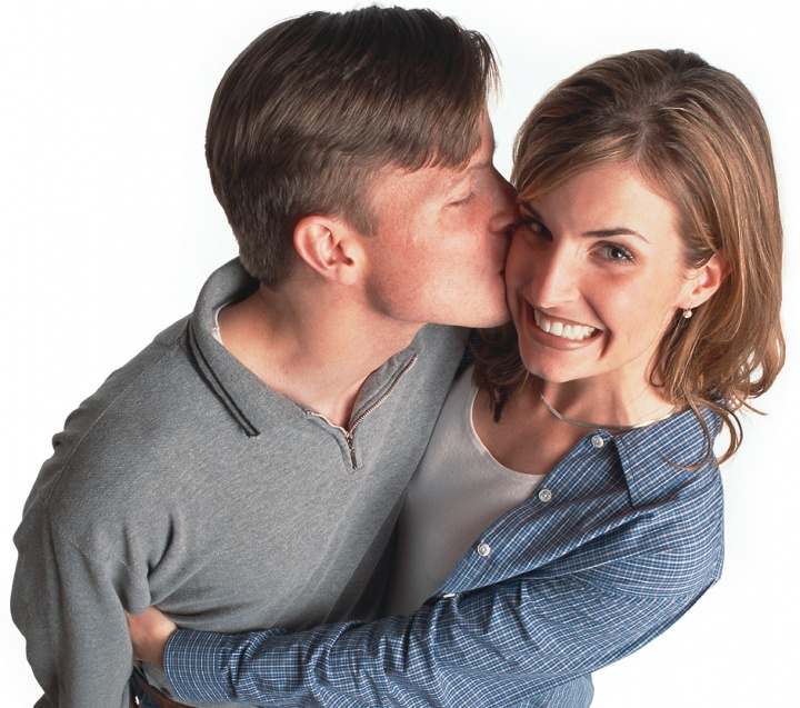 A young man kissing a young woman who is hugging him.