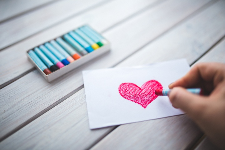 A person drawing a red heart with a crayon.