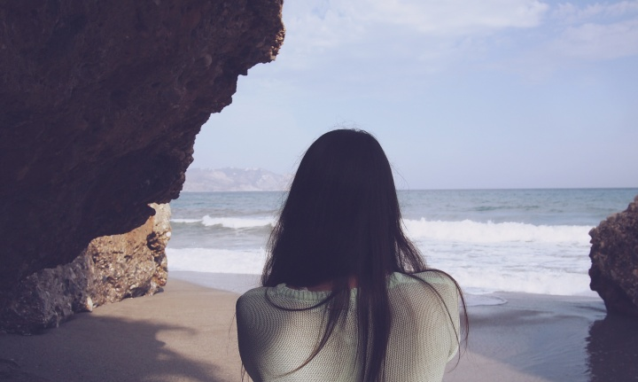 A woman looking at the ocean.