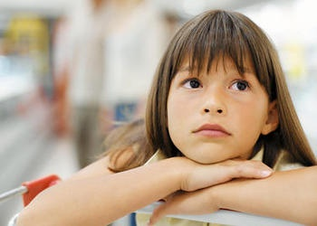 A young girl leaning on a shopping cart.